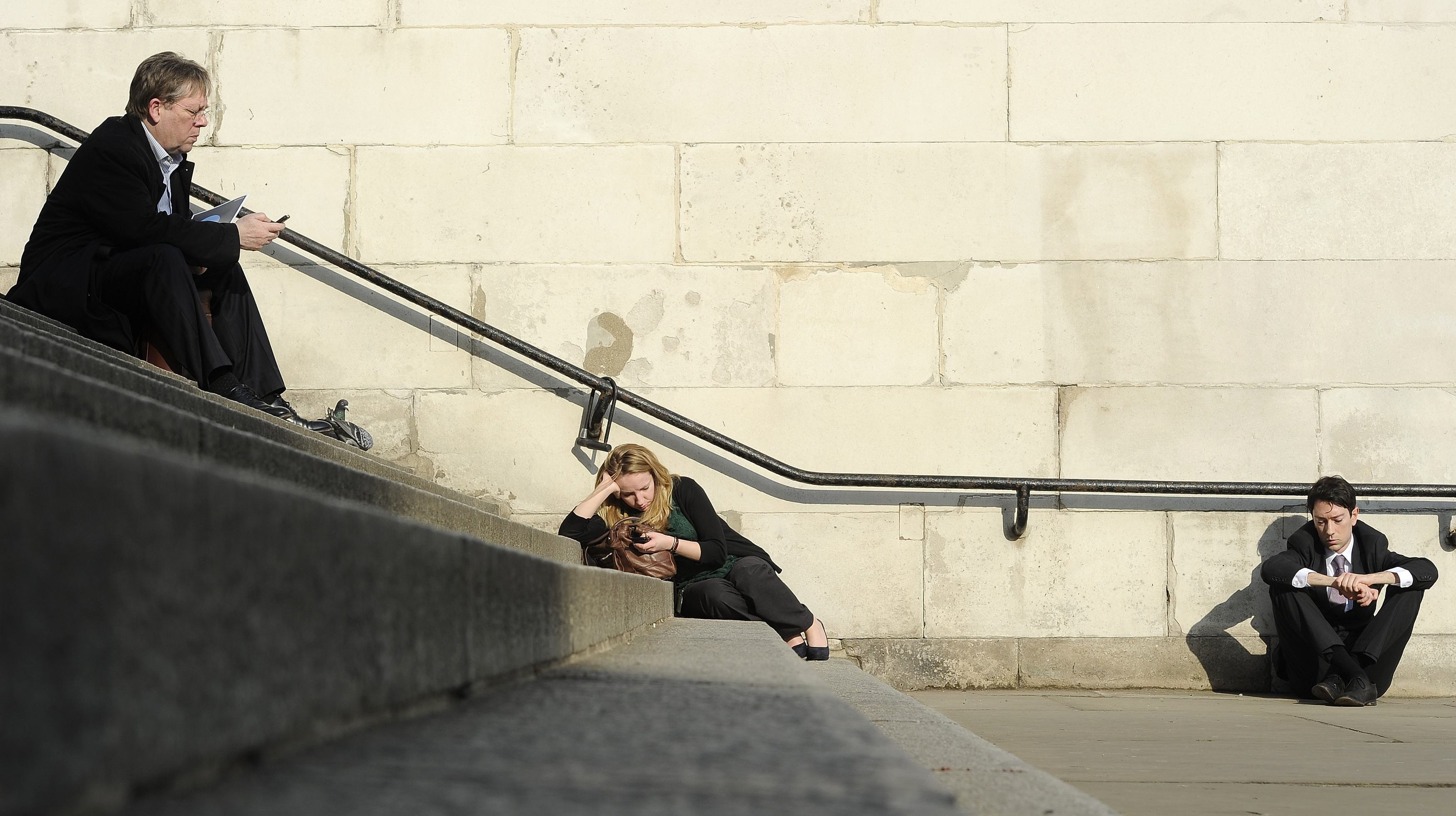 People sit in the sunshine in central London March 1, 2012. REUTERS/Paul Hackett